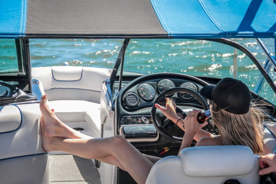 woman-wearing-black-cap-holding-bottle-on-white-speedboat-209978 (1).jpg
