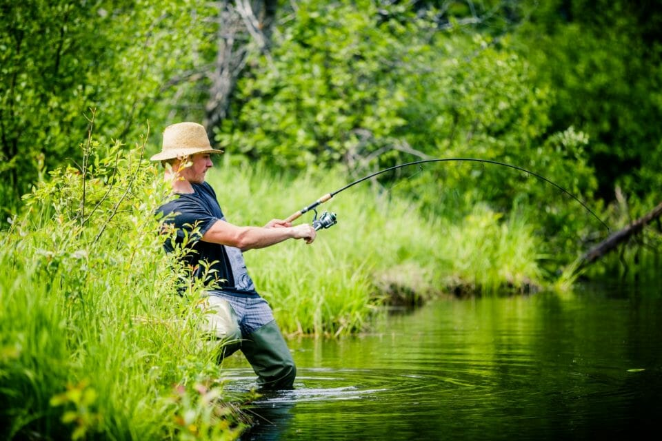 A person fishing in a river Description automatically generated with medium confidence