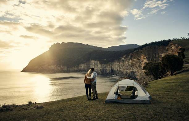This is the perfect campsite Rearview shot of an affectionate young couple standing beside their tent while camping in the mountains camping stock pictures, royalty-free photos & images